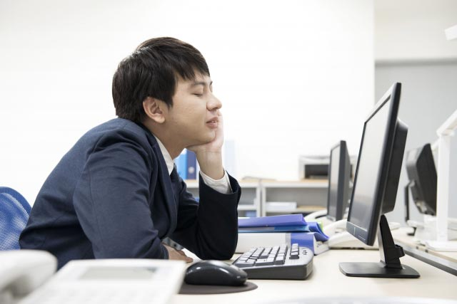 Man sleeping at work desk.