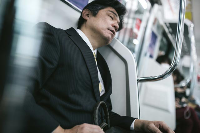 Salaryman sleeping on train